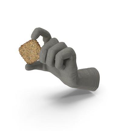 Guante que sostiene una pequeña galleta de rombos con semillas