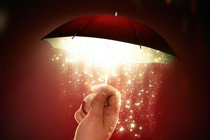 hand holds a bright umbrella with a magical glow