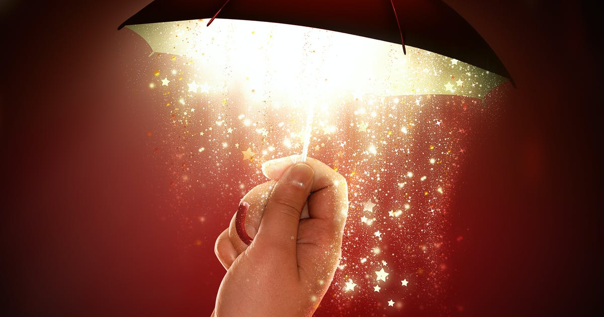 Download hand holds a bright umbrella with a magical glow by Zffoto