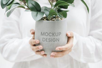 Woman holding a gray plant pot mockup