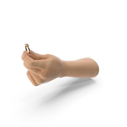 Mano sosteniendo un anillo de oro con diamante rectangular grande