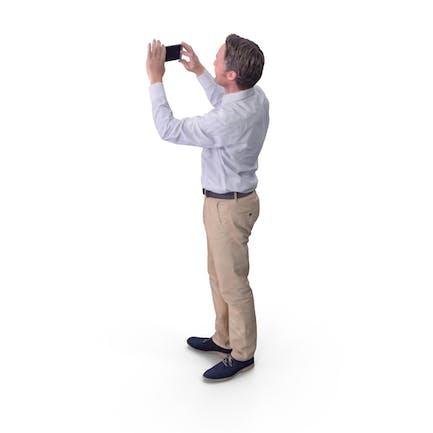 Mann beim Fotografieren mit Telefon